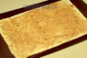 Перекладываем тесто на большую доску или другую плоскость, где будем собирать слои. Половину ореховой начинки наносим кулинарным шпателем по всей поверхности тонким слоем.