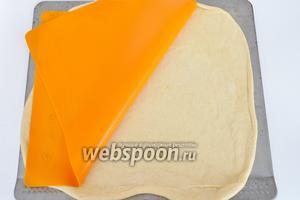Раскатать тесто и с помощью силиконового коврика переложить на лист.