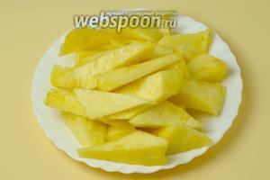 Вырезаем из ананаса мякоть клинышками, сохраняя оболочку неповрежденной.