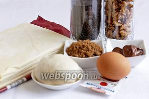 Для пирога понадобятся такие продукты: тесто слоёное дрожжевое, тесто пельменное, сахар коричневый, сахар белый, яйцо, шоколадная паста, ванилин, апельсиновая цедра, мак, орехи.