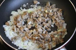 Добавить грибы, продолжая лёгкое обжаривание.