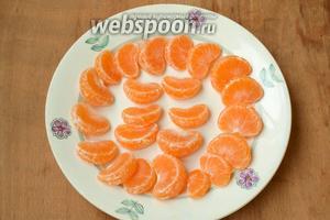 Мандарины очистить от шкурки, разделить на дольки и выложить на тарелку подсохнуть на 1 час.