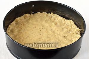 Форму диаметром 22 см смазать маслом и на дно выложить тесто, разровняв его руками.