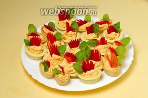 Наполняем тарталетки рыбно-сырной массой с помощью кондитерского мешка или шприца, украшаем «гребешком» из перца и зелёным листиком. Если масса успела разогреться во время приготовления, непродолжительно охлаждаем тарталетки в холодильнике и затем подаём.