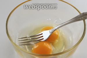 В миску вбить яйца, посолить и слегка взболтать вилкой.