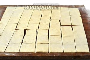 Раскатать тесто  очень тонко на слегка подпыленной мукой доске. Порезать тесто на квадратики со стороной 2-2,5 сантиметра.