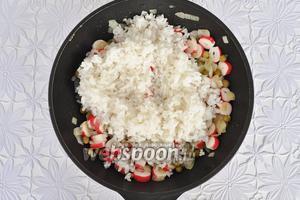 Выложить рис, перемешать, посолить по вкусу и обжарить на сковороде. На этом этапе может потребоваться добавление ещё ложки масла.