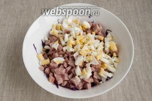Яйца почистить, нарезать кубиками и также добавить в салат.