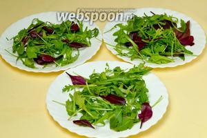 Выкладываем на порционные тарелки по горсти салатной смеси из рукколы и мангольда.