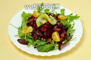 На каждую тарелку кладём горку свеклы с киви, поливаем оставшимся соусом. Украшаем четвертинками помидоров черри и долькой киви. Подаём салат сразу же.
