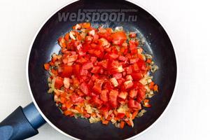 Помидор нарежем кубиками, добавим к обжаренным овощам.