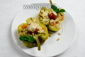 Готовые перцы разложить в тарелки. Полить соусом, посыпать орешками. Подавать горячими к обеду как самостоятельное блюдо.