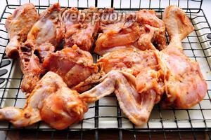 Выкладываем кусочки в маринаде на решётку в один слой или распластываем целую курицу, надрезанную вдоль грудки.