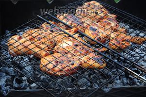 Обжариваем куриный шашлык на мангале, периодически переворачивая решётку. Как только кусочки зарумянятся и при накалывании перестанут выделять мутный сок, убираем с мангала.
