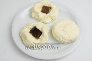 Отделить от теста кусок, сформировать лепёшку, вложить в середину начинку из кусочка шоколада, защипнуть. Сформировать сырник.
