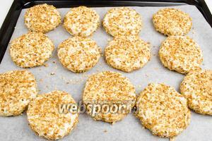 Разложить заготовки сырников на пергаментную бумагу. Поставить противень в горячую духовку. Запекать сырники в течение 25 минут при температуре 180°С.