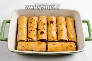 Выложить блинчики в жаропрочную посуду. Полить их топлёным маслом. Поставить в горячую духовку. Запекать при температуре 180°С в течение 15-20 минут до румяности.