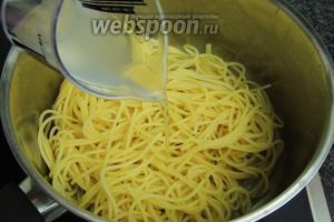 В кипящую воду с солью кладём спагетти и варим аль-денте. Сливаем воду, но 100 мл оставляем в сторону. Возвращаем спагетти в кастрюлю и вливаем 100 мл оставленной воды.