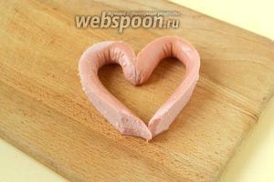 Разворачиваем концы сосиски и соединяем их в сердечко. Для того, чтобы оно не разворачивалось, на время скрепляем зубочисткой. Величину «сердечка» регулируем под размеры выемки в хлебе, лишние концы срезаем.