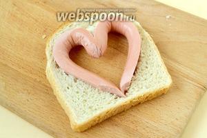 Вставляем «сердечко» из сосиски в хлеб. Теперь хлеб будет удерживать форму сердца и зубочистку можно убрать.