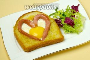 Подаём яичницу, выложив на тарелку и, по желанию, дополнив зелёным салатом, свежими овощами, соусом и т.д.