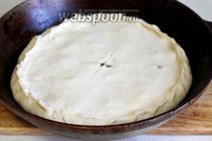 Второй кусок теста также сделать руками тонкой лепёшкой и накрыть пирог, залепляя прочно края, прорезать ножом отверстие для выхода пара, можно ещё сделать проколы вилкой (если тесто поднимется пузырем, то его нужно осторожно проколоть). Поверхность пирога смазать яйцом или маслом.