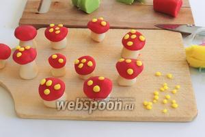 Из жёлтого марципана слепим маленькие шарики и приклеим их на шляпки. Затем шляпки оденем на ножки и немного придавим.