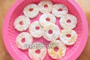Выложите на дно формы для пирога ананасы. Если сомневаетесь, что тесто не прилипнет, можно немного смазать форму сливочным маслом.
