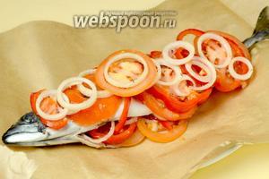 Расстилаем лист фольги, а на него — бумагу для выпечки. Кладём скумбрию на бумагу, часть овощей вкладываем в брюшко, другую — сверху рыбы.
