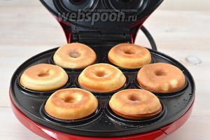 Разогреть аппарат для приготовления пончиков и в каждую ячейку вливать 1 столовую ложку теста. Выпекать пончики 2-3 минуты до готовности.