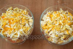 Яйца натереть на тёрке, оставив одну половинку для украшения. Выложить поверх огурцов вторую часть сыра, посыпать натёртыми яйцами.