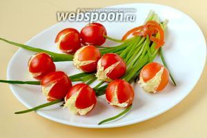 На большое блюдо укладываем пучок зелёного лука. Из полоски помидора формируем подобие ленточки, перевязывающей «букет». Укладываем нафаршированные помидоры в свободном порядке, чтобы получился букет тюльпанов. Подаём закуску к столу.