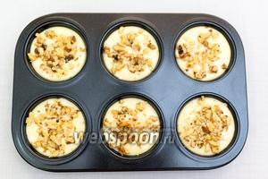 Формочки для кексов запоняем на 2/3 и присыпаем орехами.  Вторую партию я присыпала кокосовой стружкой. Выпекаем в разогретой до 190°C духовке 20-25 минут.