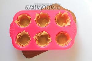 Силиконовую форму смазать сливочным маслом. Для одной корзиночки уложить в каждую ячейку по 3 квадрата теста.