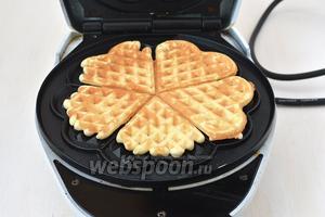 На середину разогретой вафельницы выкладывать по две столовых ложки теста и выпекать вафли на протяжении 1,5-2 минут.