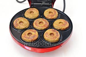 Аппарат для приготовления пончикив разогреть. В каждую ячейку выложить по полной столовой ложке печеночной массы. Закрыть крышку и готовить приблизительно 2 минуты до готовности пончиков.