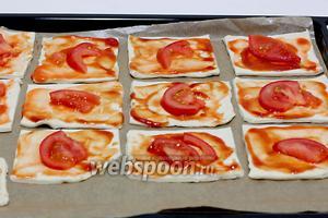 Выложить квадратики теста на противень с пергаментом. Смазать соусом (это может быть и обычный кетчуп с чесноком), сверху положить по кусочку помидора.