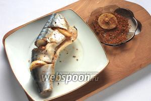 Лук порезать кольцами и обмакивая в специях вставить в надрезы рыбы.