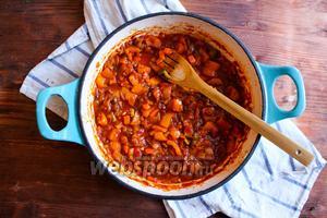 Теперь добавьте к овощам томатную пасту и томаты с томатным соком. Увеличьте огонь, посолите и поперчите пасту. Приправьте её паприкой, базиликом, орегано и добавьте 1 ст. л. сахара. Перемешайте и попробуйте соус. Вкус должен быть достаточно пряный, немного сладковатый. Если соус кисловат — добавьте ещё немного сахара. Когда соус закипит, уменьшите огонь, накройте сковороду крышкой и томите в течение 30 минут, пока соус не станет густым, а перцы мягкими. Если вода быстро выпарится плесните в соус пол стакана горячей воды и продолжите готовить. В это время отварите спагетти до состояния аль денте и откиньте на дуршлаг. Сохраните 1/2 стакана воды от варки пасты. Позже мы добавим эту жидкость в соус.