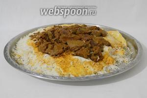 Затем сковороду накрываем подносом и резко переворачиваем её верх дном. Так рис окажется внизу, а мясо сверху.
