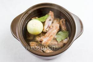 Добавить душистый перец и лавровый лист. Залить мясо горячей водой, чтобы она слегка покрыла рёбра. Поставить на медленный огонь. Тушить в течение 30 минут.