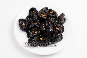 Через время вынуть чернослив из вина и начинить его орешками.