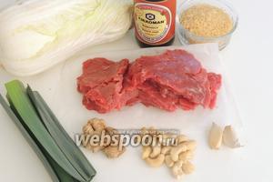 Подготовим ингредиенты: молодую говядину-минутка, нарезанную тонкими ломтиками, рис, капусту пекинскую, свежий имбирь, орехи кешью, зубки чеснока, лук-порей, кунжут и кунжутное масло, соевый соус, красный чили.