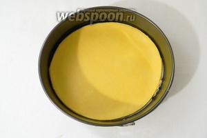 Песочное тесто раскатываем в пласт 3 мм и вырезаем из него круг по диаметру формы. Форму для выпечки выстилаем пергаментом и выкладываем на него тесто.