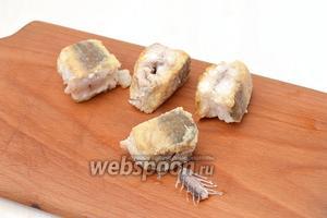 Выложить готовые кусочки рыбы на кухонную доску и нажать с одной стороны на косточку — она легко пройдёт сквозь мякоть рыбы и выйдет с другой стороны. Так мы легко избавимся от костей, оставив кусочки рыбы целыми.