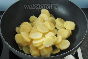 Тем временем нарезаем картофель пластинками толщиной около 3 мм и кладём в горячее масло — 1 ст.л.