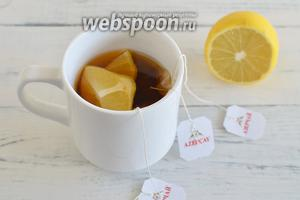 Готовим пропитку. Заварите чайные пакетики в 100 мл кипятка, добавьте 2 дольки лимона и сахар, перемешайте.