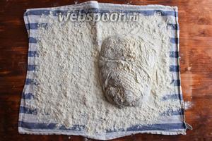 Отставьте тесто в сторону и расстелите на столе чистое сухое кухонное полотенце. Присыпьте его мукой и переложите на него тесто швами вниз.