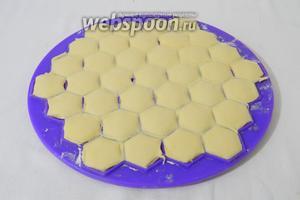 Аккуратно скалкой раскатываем тесто на пельменнице. Удаляем обрезки.