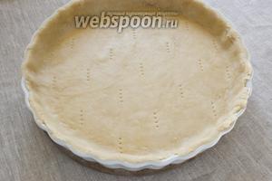 Тесто раскатать в пласт по площади немного больше формы для выпечки. Поместить в форму для выпечки, формируя бортики. Сделать наколы вилкой.